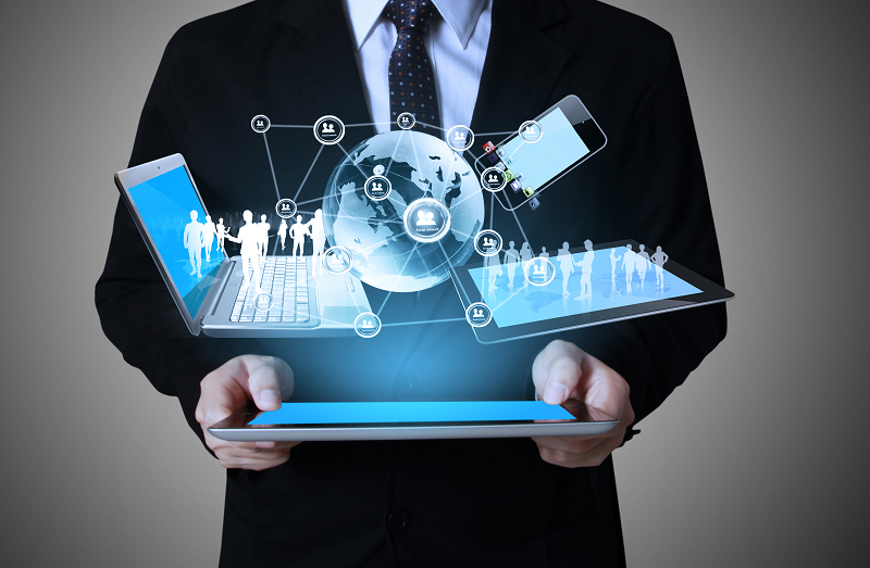 Man Holding Tablet With Globe And Laptop And Phone Hovering | Managed IT Services | SkyViewTek