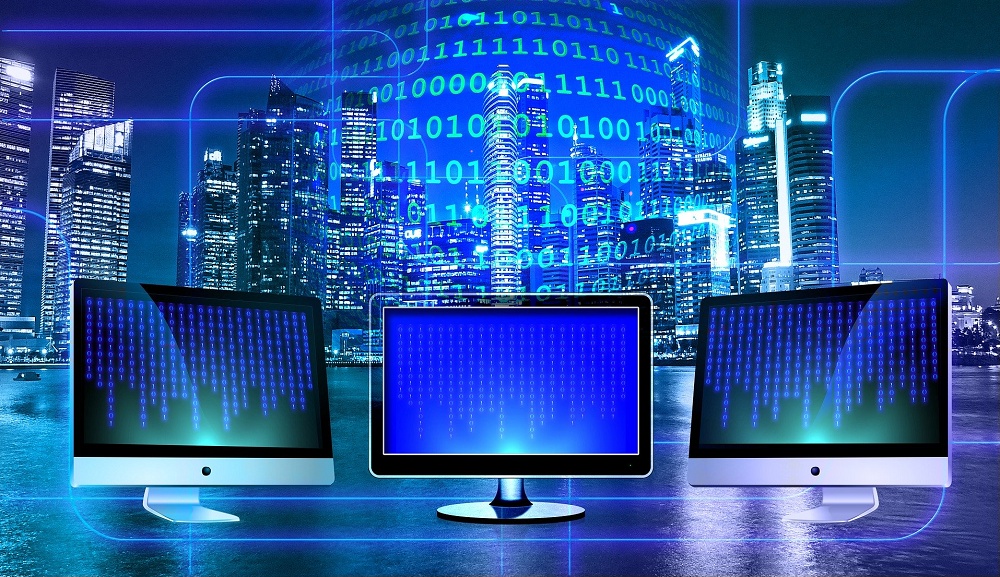 Three Monitors In Front Of A Window Showing A City Skyline And Overlaid By Binary Code-SkyViewTek Managed IT Services