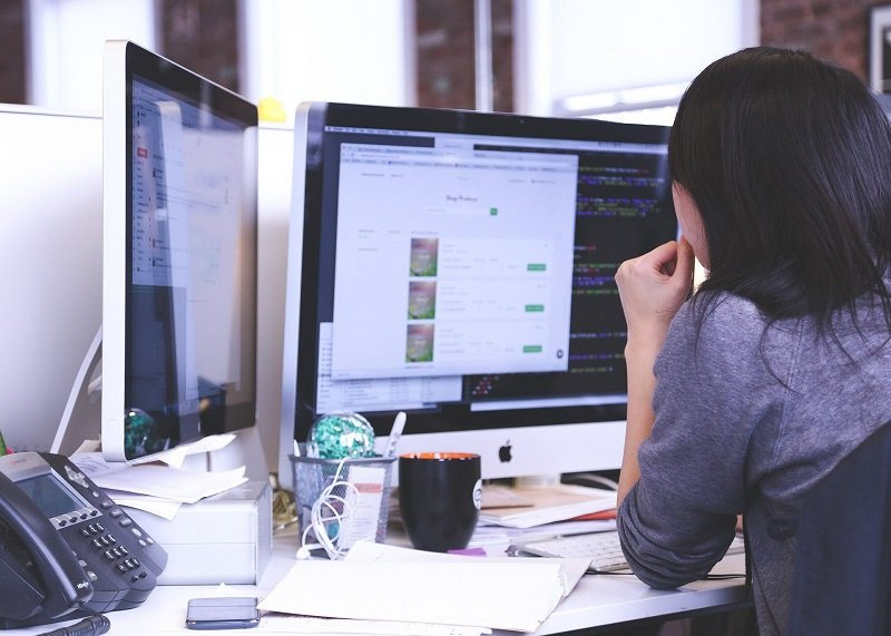 Woman sitting at an office desk working | Cloud Solutions by SkyViewTek